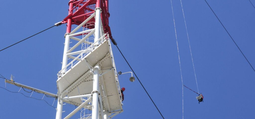Person leaning over platform of the ZOTTO tower an device hanging on ropes