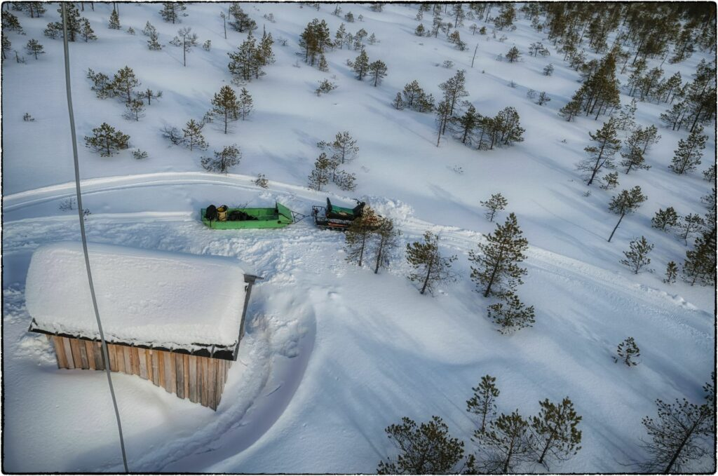 view from above on snowy hut and snowmobile