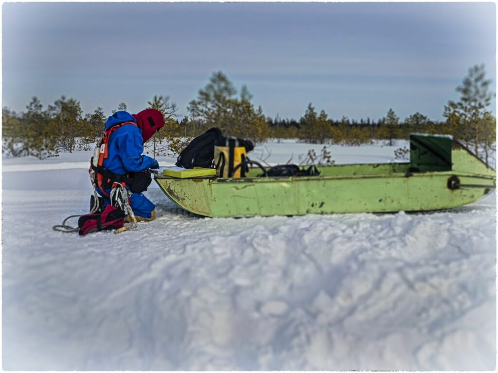 working person kneeling in snownext ti a gree snowmobile trailer