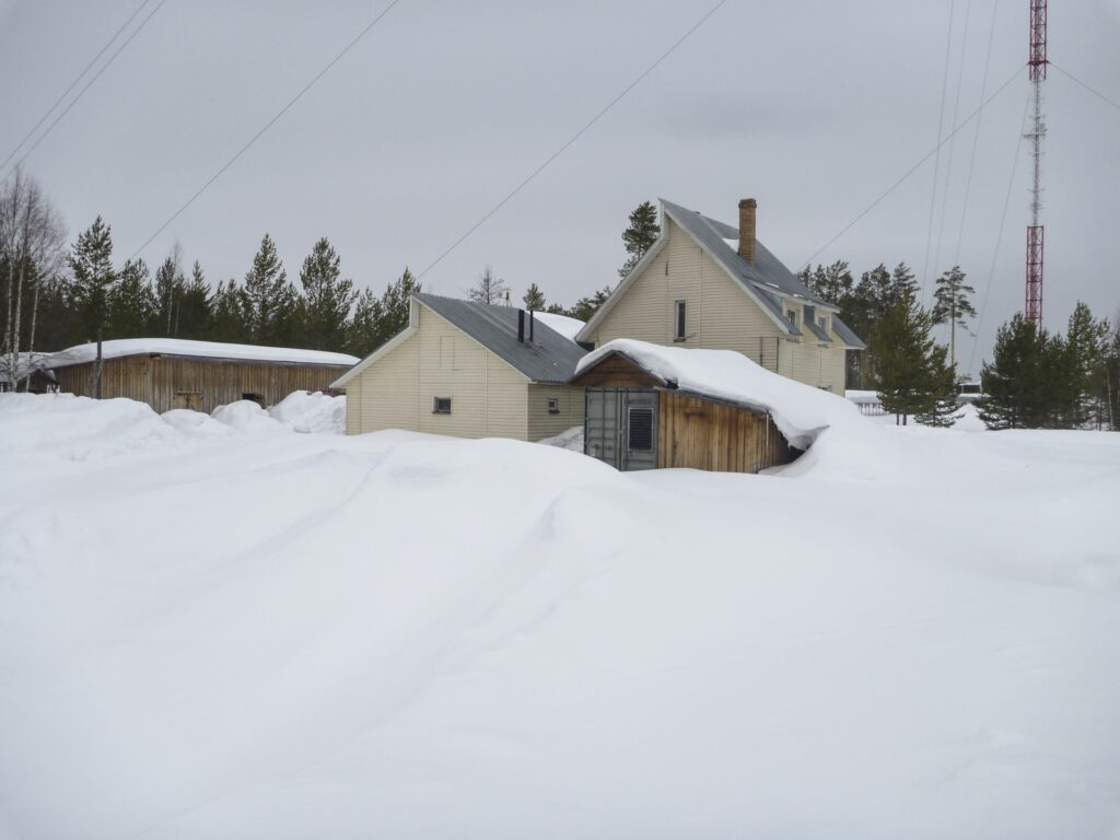 house at Zotto tall towerstation in deep snow before grey sky