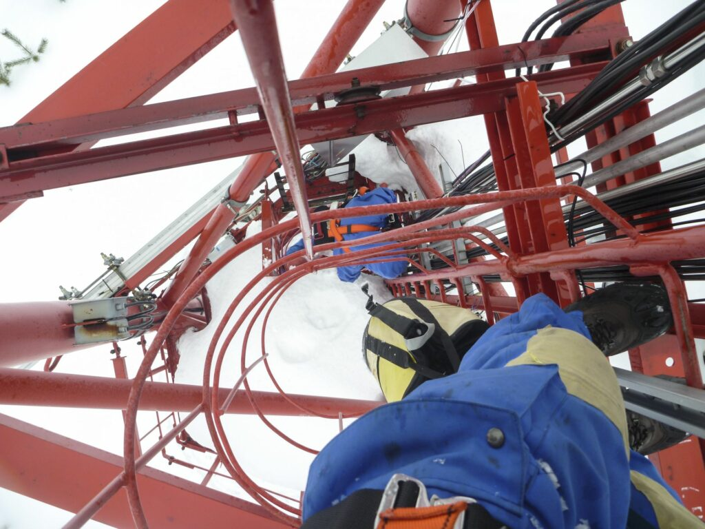 2 persons in blue snowsuits and climbing gear in the ladder shaft of the Tall Tower in freezing cold weather in winter