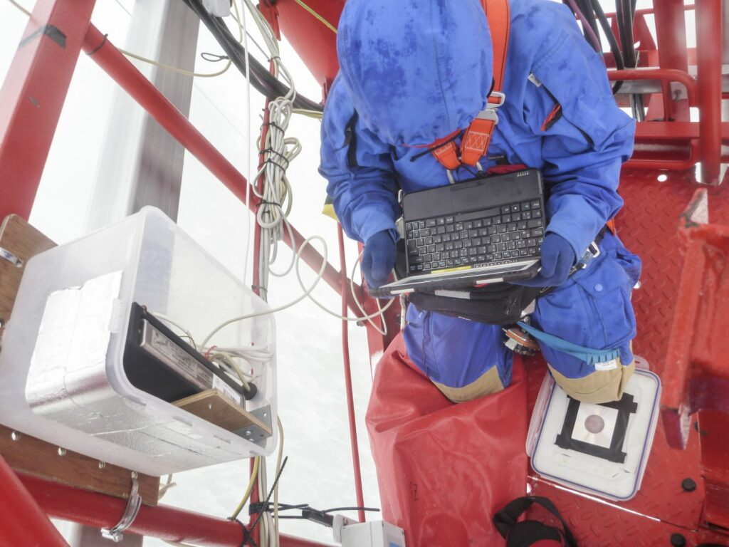 person in blue snowsuit and climbing gear sitting on the tower with notebook on his lap reading a device in cold and wet weather in winter