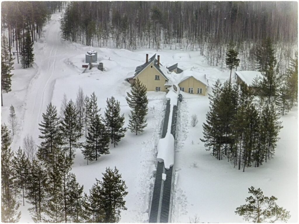 view from low height from the tower on snow-covered house and pergola in winter in Zotto