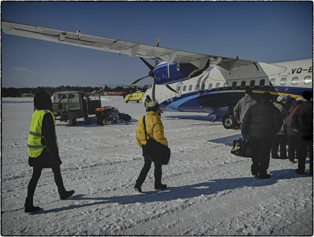 airplane in snow and waiting people