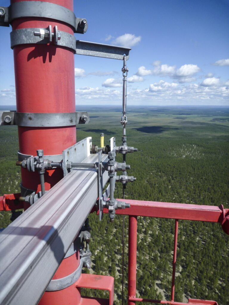 gigantic view into the distance from the top of the Tall tower with blue blue sky white clouds and green trees to the horizon