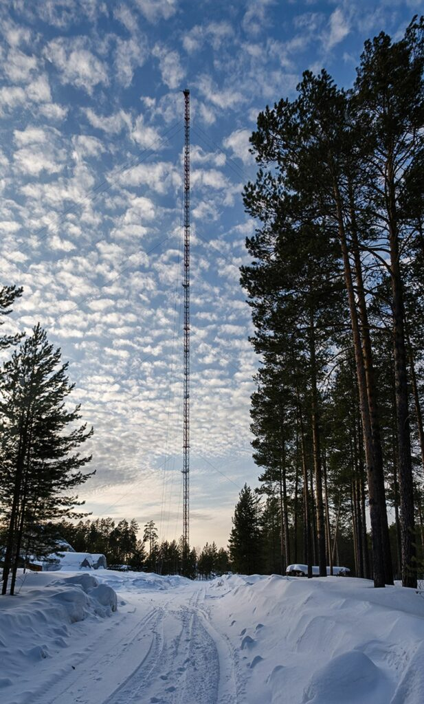 Zotino Tall Towerfrom far awayin winter with nice little clouds before blue sky and deep snow in front