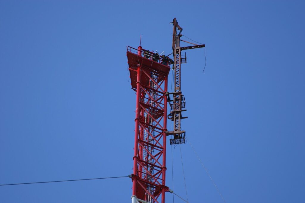 3 people and the erection-crane-on top of the so far built Zotto tall tower