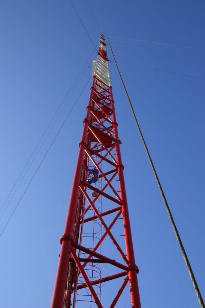 person climbing the red and white tall tower in Zotto with clear blue sky