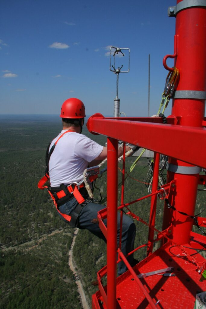 Mechanic in climbing equipment outside working high up on the tower