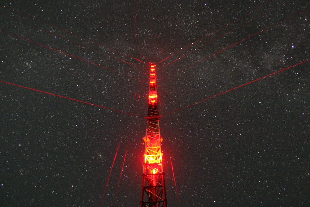 red illuminated tower before dark starry night with millions of stars