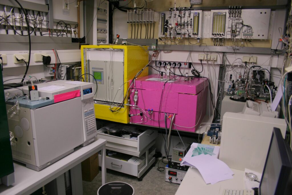various devices and big pink and yellow boxes in grey laboratory at Zotto station